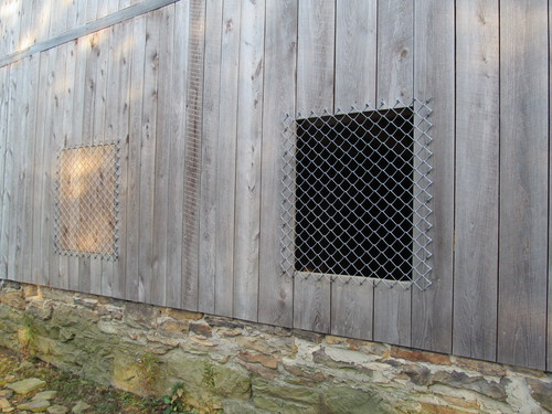 Window openings [opened and closed] covered with chain link.